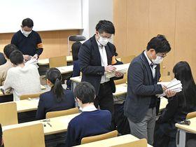 マスク姿で問題や解答用紙を配布する試験監督者=25日午前9時25分、岐阜市柳戸、岐阜大