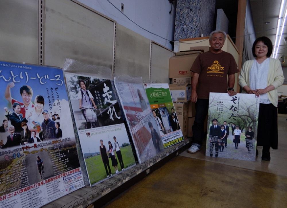 地元で撮影、スタッフも出演者も地元で。送り出したオリジナル映画のポスターを持つ菊池一俊さんと齋藤智美さん(右端)=2018年6月、茨城県那珂市