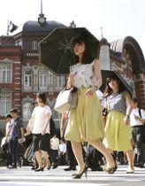 厳しい暑さの中、JR東京駅前で日傘を差して歩く女性=20日午前