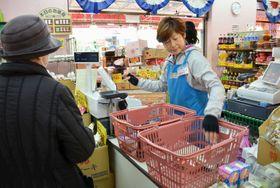食品スーパーのレジで代金を計算する店員=2016年、東京都練馬区の「アキダイ関町本店」