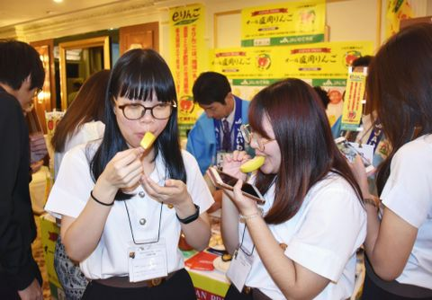 14日、バンコクで開かれた岩手県のPRイベントで、リンゴを試食するタイ人の参加者ら(共同)