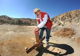 サンホセ鉱山の上に立ち、鉄管のふたにそっと手を伸ばすホルヘ・ガジェギジョス。7年前の事故の際、この穴を通じて地下に食料や手紙が届けられガジェギジョスたち作業員の命が救われた=チリ・コピアポ近郊(撮影・鍋島明子、共同)(了)