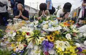 放火火災のあった「京都アニメーション」第1スタジオ近くを訪れ、手を合わせる人たち。犠牲者を追悼する多くの花束が供えられた=19日午後、京都市伏見区