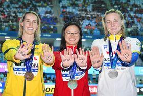 水泳の世界選手権で、闘病中の池江璃花子選手へメッセージを送る女子100メートルバタフライのメダリストたち=22日、韓国・光州(共同)