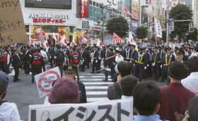 警察官が警備する中、移民政策反対を掲げてデモ行進するグループ=14日午後、東京・新橋