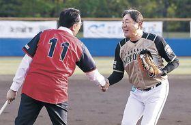 始球式を終えて握手を交わす日本ハムの荒木監督(右)と小松マテーレの池田社長=金沢市民野球場