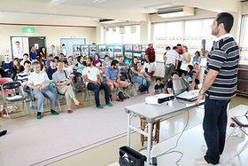 シリアの情勢を説明するサリムさん(右)=高岡市下牧野公民館