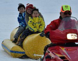 スノーモービル(手前)に引かれたスノーバナナにまたがって雪原を滑走、歓声を上げる子どもたち