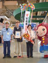 15万人目の乗船客となった下薗昭一さん(左から2人目)と妻和子さん(同3人目)=鹿児島市の鹿児島港桜島フェリーターミナル