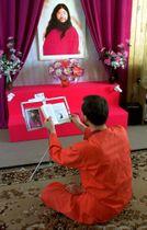 ロシア西部ウラジーミル州のオウム真理教施設で教祖の写真を前に修行する男性=2000年2月(タス=共同)