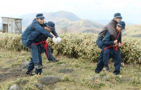 ロープで負傷者を背中にくくりつけて搬送する美作署員