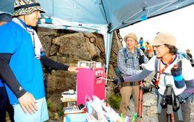 石鎚山の頂上広場に開設された臨時郵便局のポストにはがきを入れる登山客=11日午前11時50分ごろ