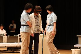 高齢者役をいすに誘導する生徒=大村市幸町、シーハットおおむら