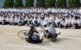 スマートフォンを使いながら走っていた自転車と歩行者の衝突事故を実演し、高校生に注意を呼び掛ける熊本南署員=20日、熊本市西区の熊本西高