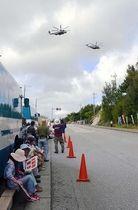 辺野古新基地建設に反対し、座り込んで集会を開く市民らの上空を飛び交う米軍ヘリ2機=5日午前9時6分、名護市辺野古の米軍キャンプ・シュワブゲート前
