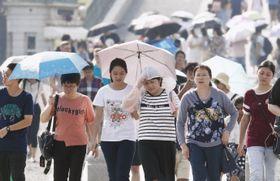 厳しい暑さの中、皇居前で色とりどりの傘を差して歩く外国人観光客ら=17日午後、東京都千代田区