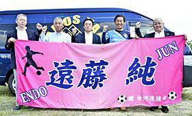 遠藤選手の父淳さん(右から2人目)に応援用の横断幕と激励金を手渡す深谷会長(中央)ら