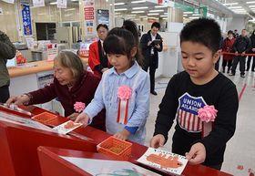 年賀状の投函に一番乗りした石川さん(左)と蜆貝保育園の園児=15日午前、青森市の青森中央郵便局