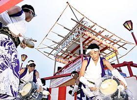 回転するやぐらをバックに念仏踊りを披露する下綴青年会メンバーたち