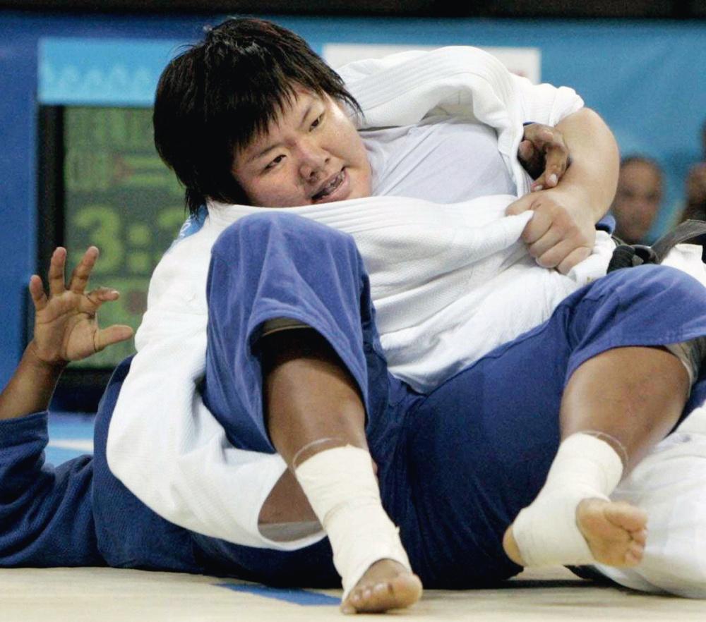 2004年アテネ五輪の柔道女子78㌔超級で、塚田真希はキューバ選手を後ろけさ固めで破り金メダルを獲得(共同)
