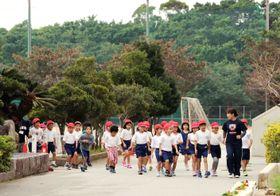 沖縄県宜野湾市立普天間第二小で行われた、米軍ヘリの接近を想定した避難訓練に参加する児童=18日午前