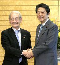 表敬訪問した旭化成名誉フェローの吉野彰氏(左)と握手を交わす安倍首相=11日午前、首相官邸