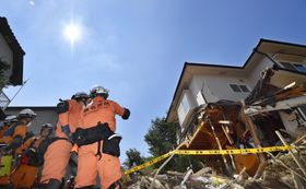 強い日差しが照りつける中、広島県熊野町の土砂崩れ現場で行方不明者を捜索する消防隊員=15日午前