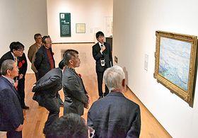 角野広海学芸員(中央奥)の案内で作品を鑑賞する来館者