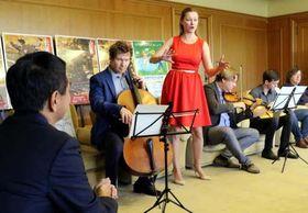村岡知事(左端)の前で歌声や演奏を披露するロシアの音楽家たち