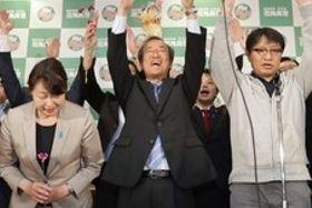 知事選で初当選が決まり、万歳する花角英世氏(中央)=10日午後10時30分すぎ、新潟市中央区