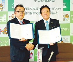 握手を交わす桜井市長(右)と上畠局長