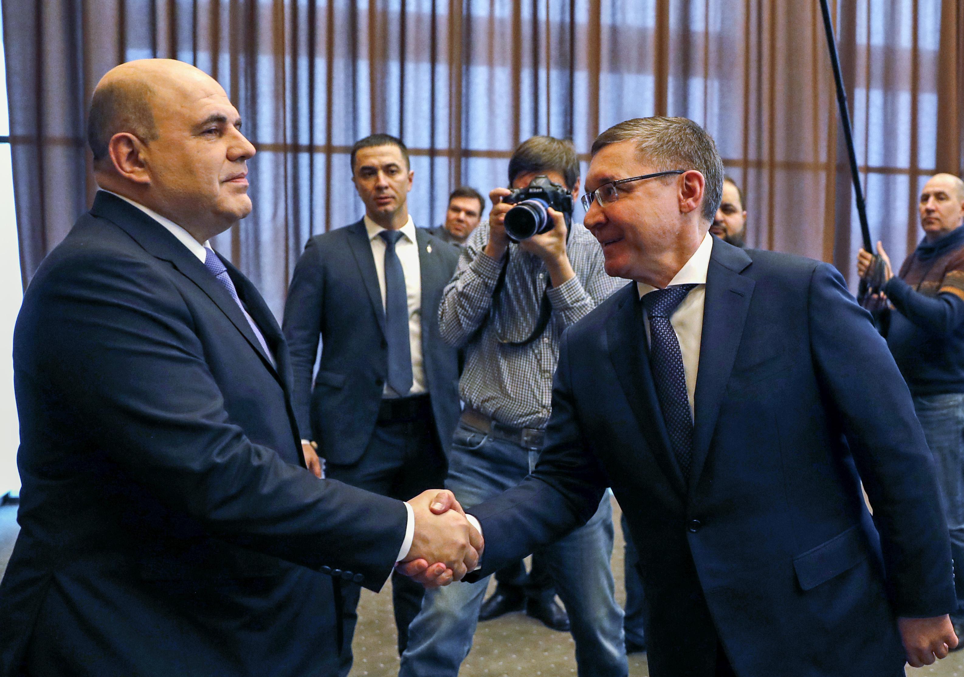 ロシア西部ヤロスラブリ州でイベントに出席し、ミシュスチン首相(左)と握手するヤクシェフ建設住宅相=3月13日(タス=共同)