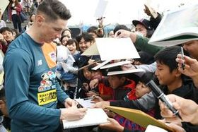 大勢のファンに囲まれ、サインに応じるフェルナンド・トーレス選手=沖縄県の読谷村陸上競技場
