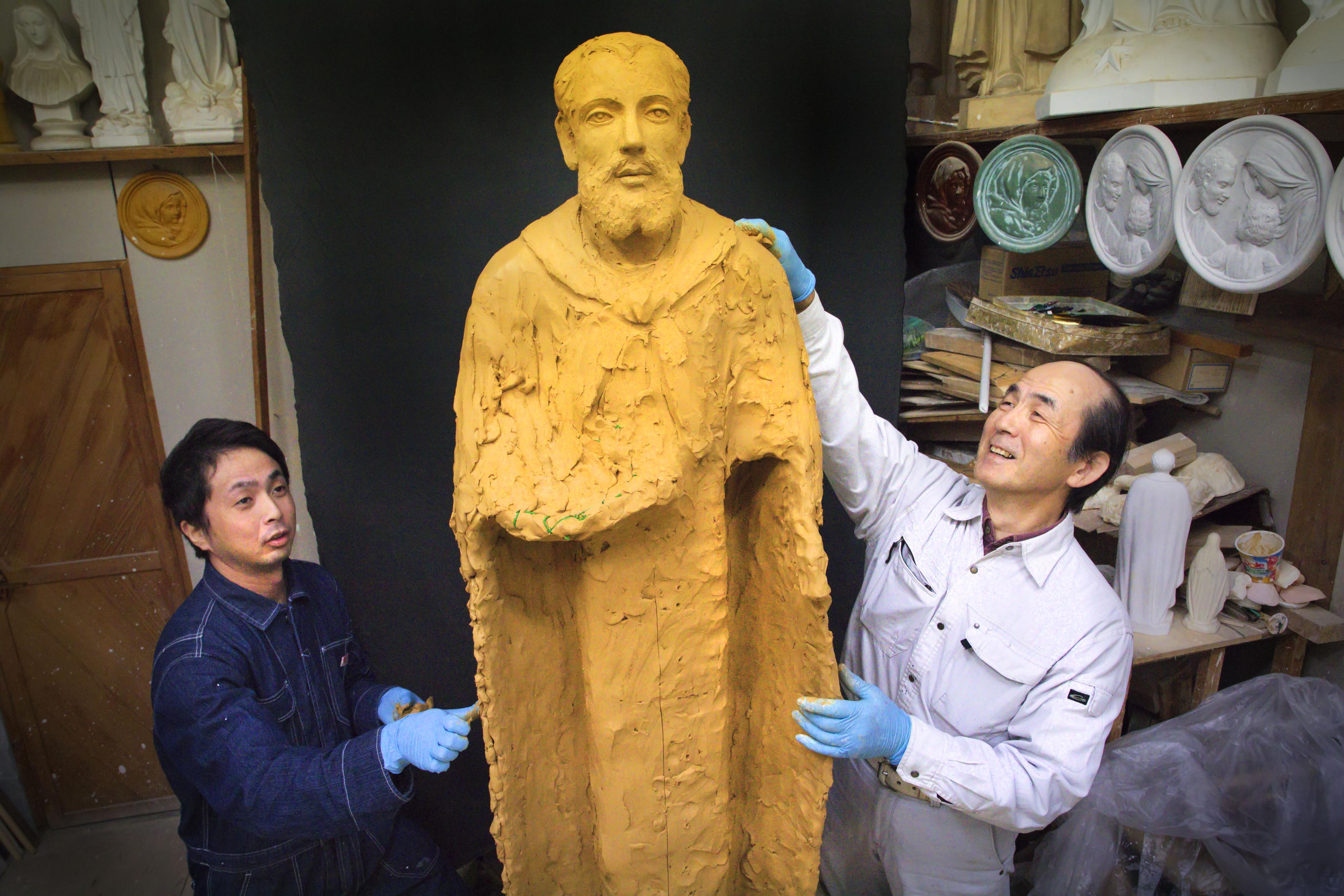 聖ペトロ像を制作する中田三穂(右)と長男和宏=長崎市の中田ザビエル工房