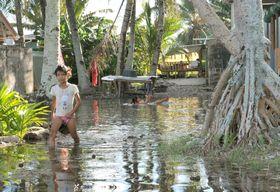 海面上昇の危険にさらされる太平洋の島国ツバルで、海水で浸水した集落を歩く少女=2014年1月(共同)