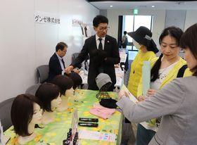 ウイッグなどアピアランスケア商品を見学する参加者ら=県庁