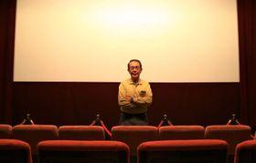 ホール・ソレイユのスクリーン前に立つ詫間敬芳社長
