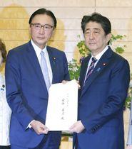 「拉致救出議員連盟」の古屋圭司会長(左)から申し入れ書を受け取る安倍首相=22日午後、首相官邸