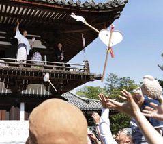 唐招提寺で、参拝客にうちわをまく僧侶=19日午後、奈良市