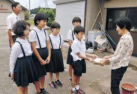 地域の高齢者に避難訓練の案内チラシを手渡す児童=珠洲市上戸町寺社