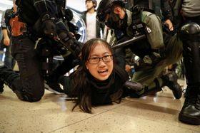 15日、香港のショッピングセンターで警察に拘束されるデモ参加者(ロイター=共同)