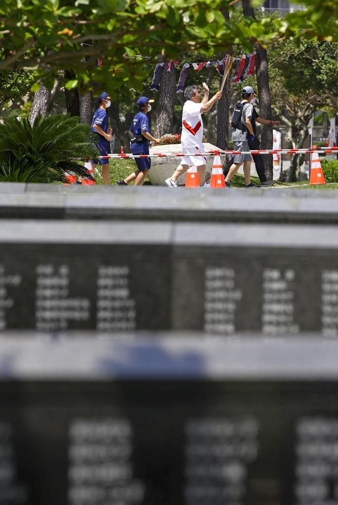 沖縄県糸満市の平和祈念公園で行われた聖火リレー。手前は「平和の礎」=2日午前