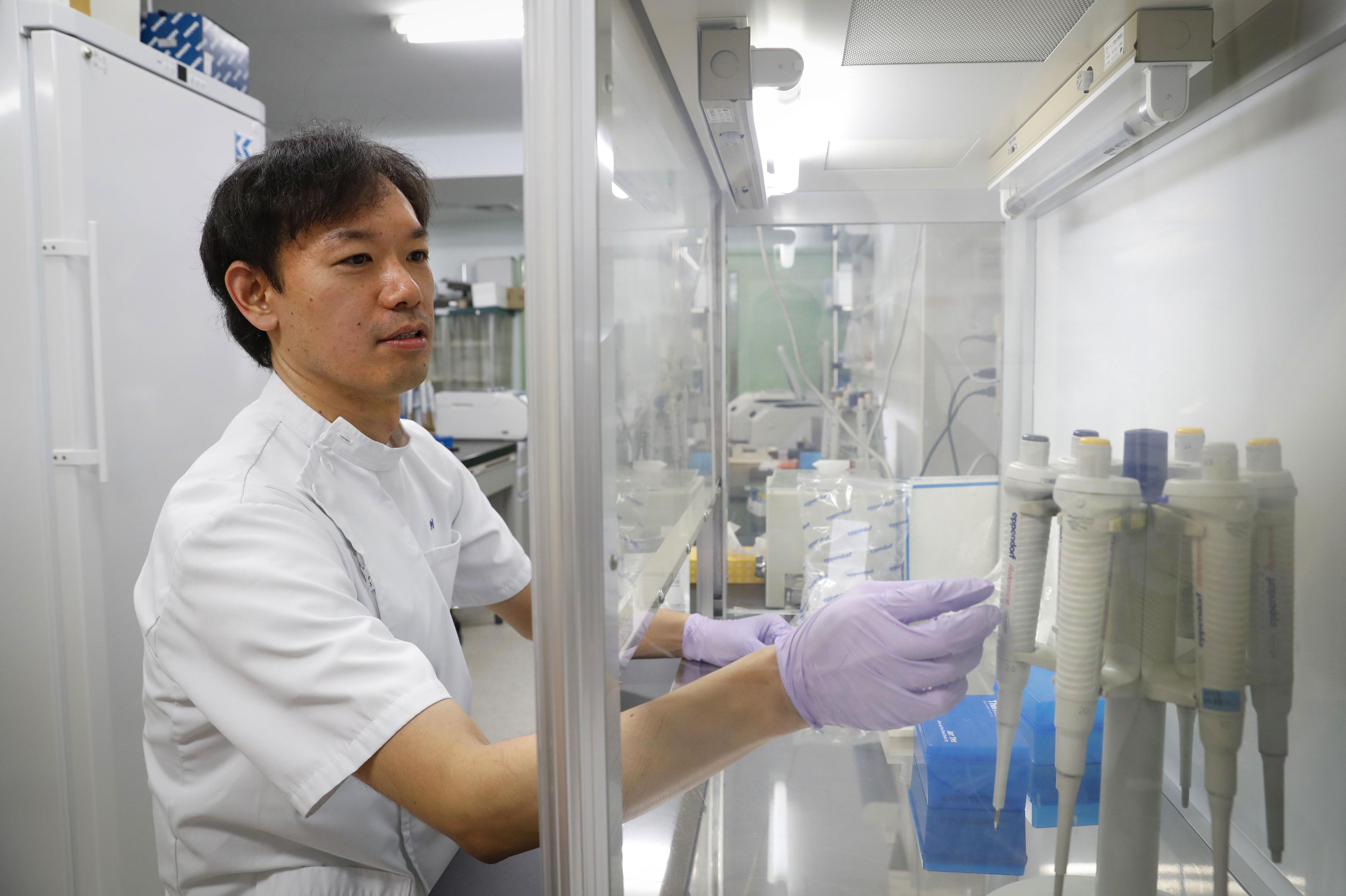 遺骨のDNAの型を調べる旭川医大准教授の浅利優。遠い血縁関係でも身元特定につなげる方法を研究している=北海道旭川市