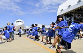 20日の「空の日」にちなんだイベントでジェット機を綱で引く小学生=23日、成田空港