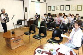 古川さん(左端)のアコーディオン演奏に合わせて歌うカナリヤの会の会員たち