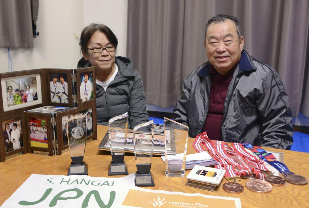 半谷静香選手のトロフィーやメダルと父良人さん、母千賀子さん=2019年11月、福島県いわき市