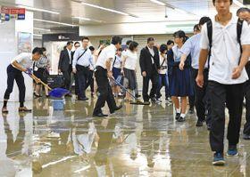 未明の大雨で地下道が浸水し、足元を気にしながら通勤する人たち=17日午前7時15分、名古屋・栄で(木戸佑撮影)