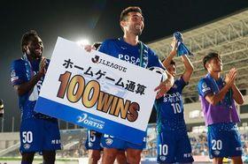 8月18日の山形戦、笑顔でホーム戦通算100勝のプレートを掲げるバラル(中央)=鳴門ポカリスエットスタジアム