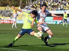 前半5分、激しく競り合う栃木SCのMF浜下(左)=県グリーンスタジアム