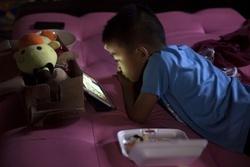 携帯端末の画面を見る子ども(ゲッティ=共同)